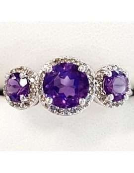 White gold ring featuring three round amethysts and diamonds